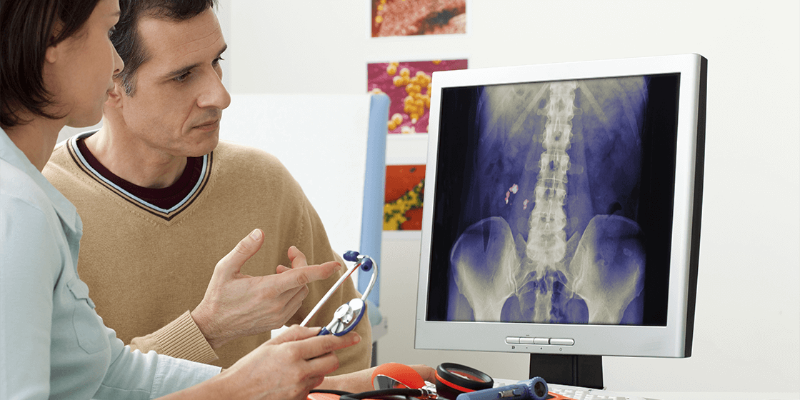 spine doctor and patient reviewing x-ray for back pain emergency